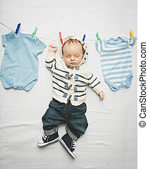 little baby boy in jeans hanging on cord next to drying clothes