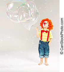 Funny picture of little clown making soap bubbles