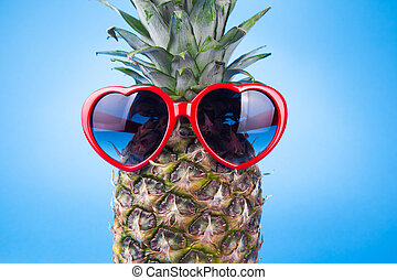 Funny pineapple in a sunglasses on yellow background