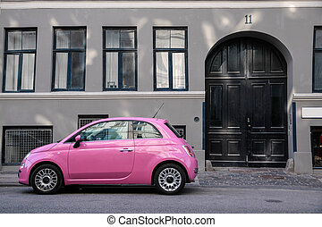 Funny pink car in front of a gray house in Copenhagen, Denmark