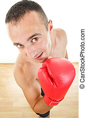 man with boxing gloves looking at the camera if is anyone there