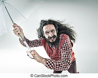 Funny portrait of a nerdy guy holding an umbrella