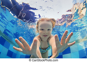 Funny portrait of baby girl swimming underwater in pool
