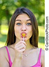 Funny portrait of girl licking lollipop