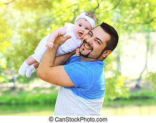 Funny positive father and baby having fun outdoors in summer day