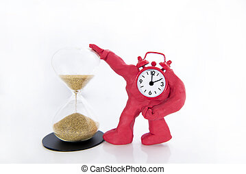 Funny red Clock with hourglass on white table. Daylight Saving Time Concept.