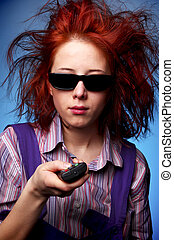 Funny red-haired girl in glasses with TV remote