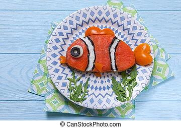 Funny salmon sandwich for kids lunch on a table