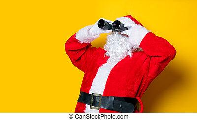 Funny Santa Claus holding binoculars