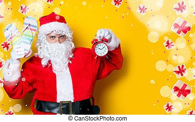 Santa Claus holding flip flops and alarm clock