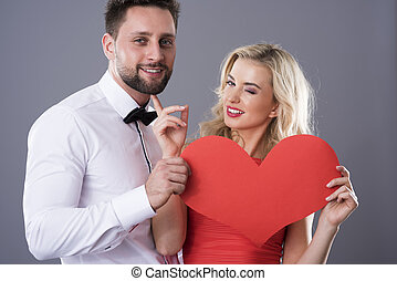Funny scene of man and woman with paper heart