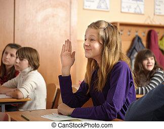 Funny schoolgirl is raising up her hand