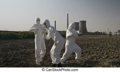 Funny scientists in hazmat suits dancing and fooling around near the location of a refinery celebrating successful mission