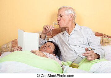 Funny senior couple in bed
