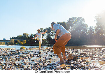Funny senior couple playing with water at the river in a sunny d