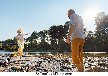 Funny senior couple playing with water at the river in a sunny day