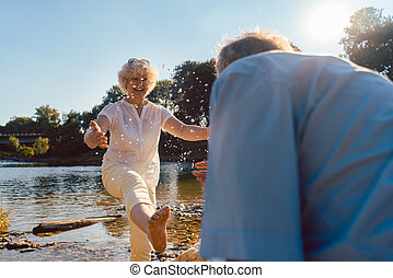 Funny senior couple playing with water at the river in a sunny day of summer