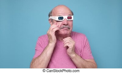 Funny senior hispanic man in special glasses watching melodrama crying.