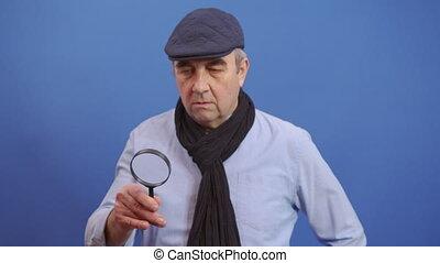 Funny Senior Old Man using Magnifying Glass