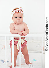 funny, seven month old baby girl standing in her bed