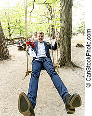 Funny shot of bride swinging screaming groom on the swing at park