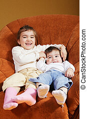Funny sisters sitting in chair
