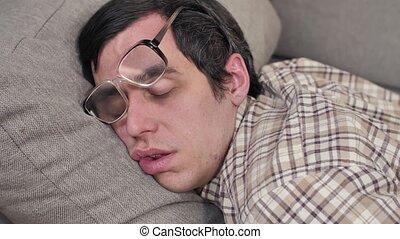 Funny sleeping nerd on the sofa