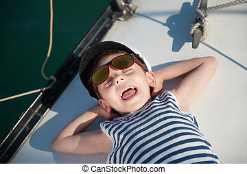 funny small kid in captain hat lying on board luxury yacht...