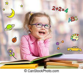 Funny smart kid in glasses reading book - Happy child girl...