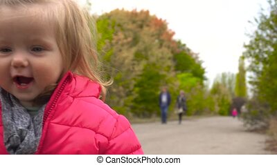Funny smiling baby girl in the park in fall