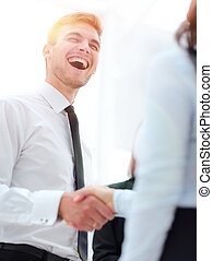 funny smiling businessman shaking hands with his partner.