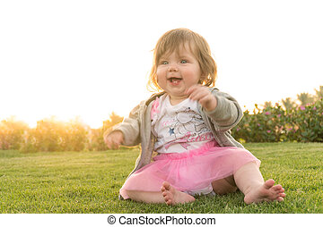 Funny smiling happy girl sitting on grass