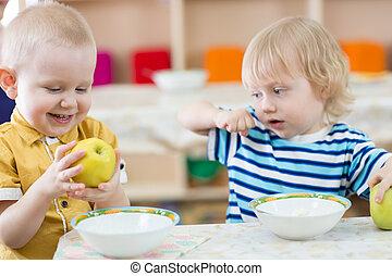 Funny smiling kid eating apple in kindergarten