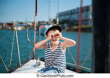 funny smiling kid in captain hat looking imitating...