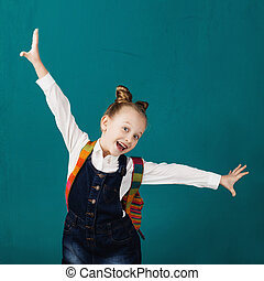 Funny smiling little girl with big backpack jumping and having fun against blue wall.