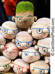 Funny souvenir bags with ground and grass seads in form of human faces. After watering the grass grows like hair