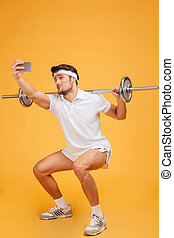 Funny sportsman exercising with barbell and talking selfie...