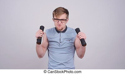 Funny sporty nerd in glasses and small dumbbells on a gray...