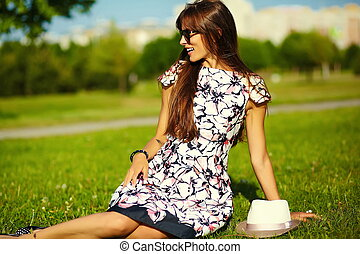 Funny  stylish sexy smiling beautiful young woman model in summer bright  hipster cloth dress  sitting on grass in the park