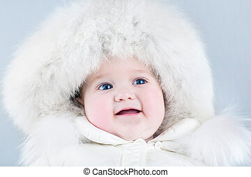 Funny sweet baby girl wearing a big fur hat and a white winter s