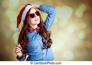 Funny teenage girl in heart shaped sunglasses and santa hat
