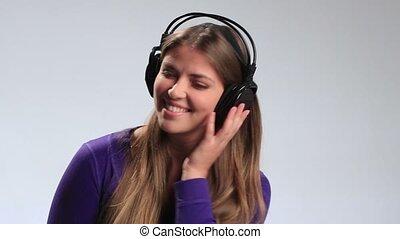 Funny teenage girl listening radio with headphones