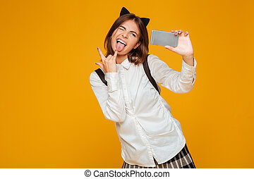 Funny teenage schoolgirl in uniform with backpack