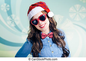 Funny teenager in heart shaped sunglasses and santa hat