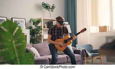 Funny teenager is having fun with virtual reality glasses wearing headset holding the guitar and moving body as if performing on stage. Nice interior is visible.