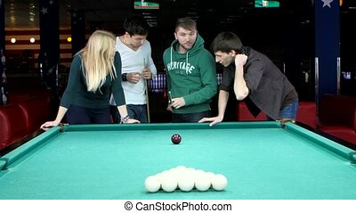 Funny time with friends in billiard club. Young man doing kick on billiard ball