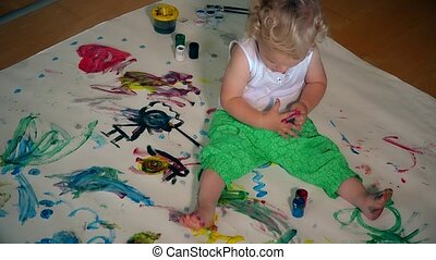 Funny toddler child with dirty hands painting on floor and clothes