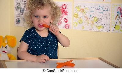 Funny toddler girl child eating carrots sitting by table in her room