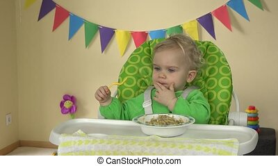 Funny toddler girl eat mash with spoon and hands sitting in baby feeding chair.