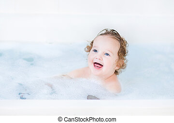 Funny toddler girl having a bath with foam